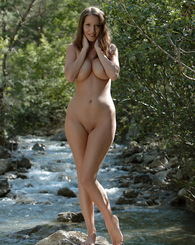 Angela posing nude on the rocks and showing of her shaved pussy and firm big tits