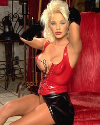 Chloe Jones dons a sexy sophistication.  Her blonde hair and knock out body are the perfect accompaniment for the red and black patent leather she so