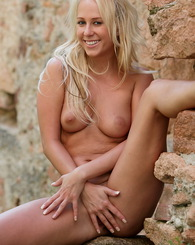 Sexy blonde babe Carla show us her firm ass and firm tits by a castle ruins
