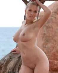 Amazing babe Janine with perfect body and natural big tits posing by the juniper tree